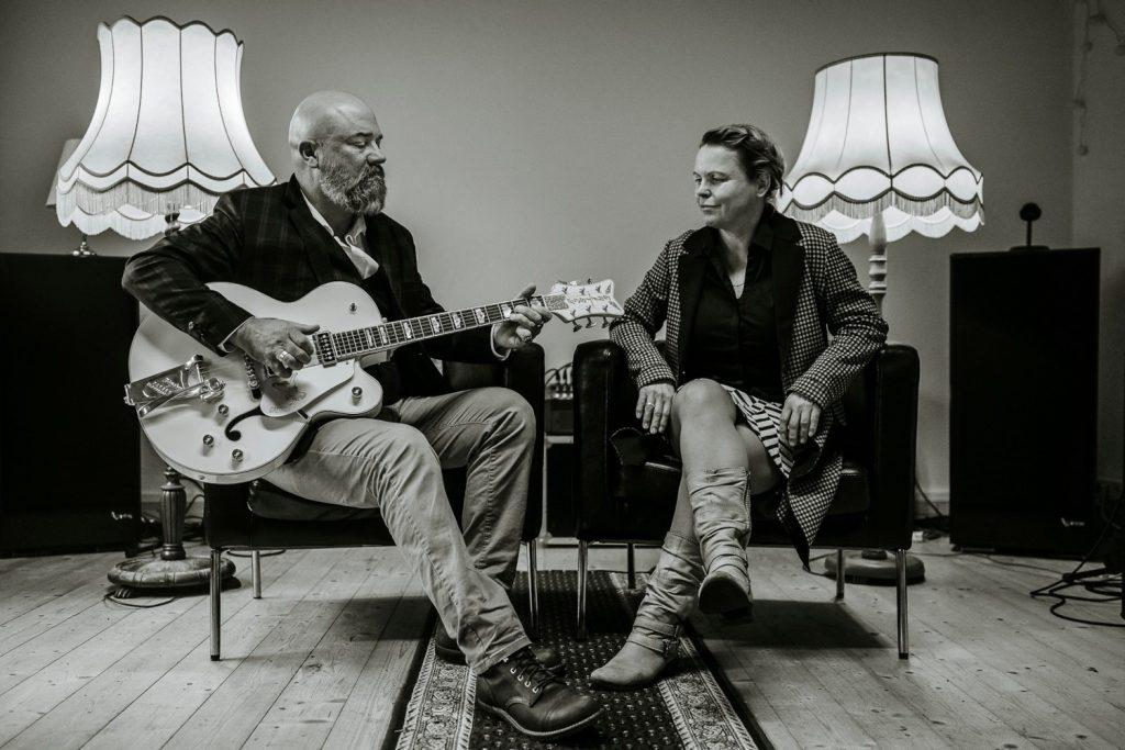 Mark und Susan sitzen nebeneinander auf zwei Sesseln, Mark hält spielbereit eine Gitarre