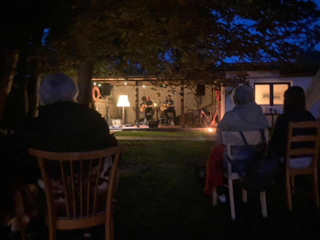 zwei Menschen spielen ein Gitarrenkonzert, im Vordergrund sieht man die Zuhörer:innen sitzen
