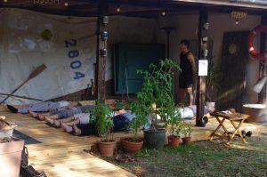 mehrere Menschen liegen während einer Yoga Übung auf dem Boden, der Anleiter steht wachsam daneben