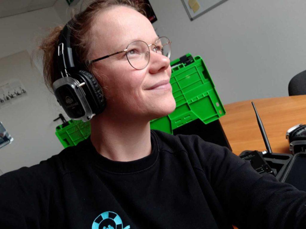 Die Autorin trägt Kopfhörer- im Hintergrund ist Equipment zu sehen