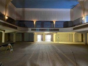 Hineinsicht in einen großen Saal mit himmelblauer Decke und einem Rang. D