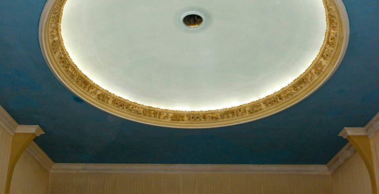 Man sieht die himmelblaue Decke des Saals. Ein Kranz goldener Engel ist beleuchtet und bildet eine Kuppel.