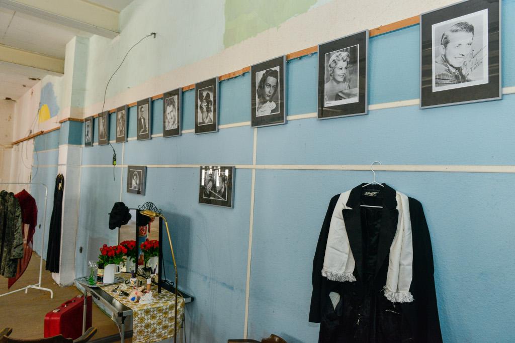 An einer unrenovierten Wand hängen zahlreiche schwarz/weiß Portraits. Eine Künstler:innengarderobe ist eingerichtet.