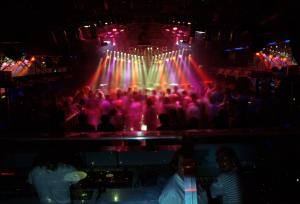 Eine aufwendige Lichtanlage beleuchtet ein feierndes Publikum in einer Discothek