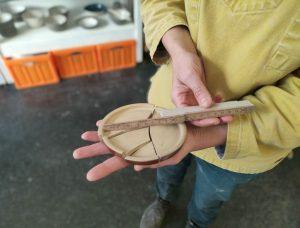 Zerbrochener Keramikdeckel auf Handfläche mit Metermaß daneben (c) Tanja Albert